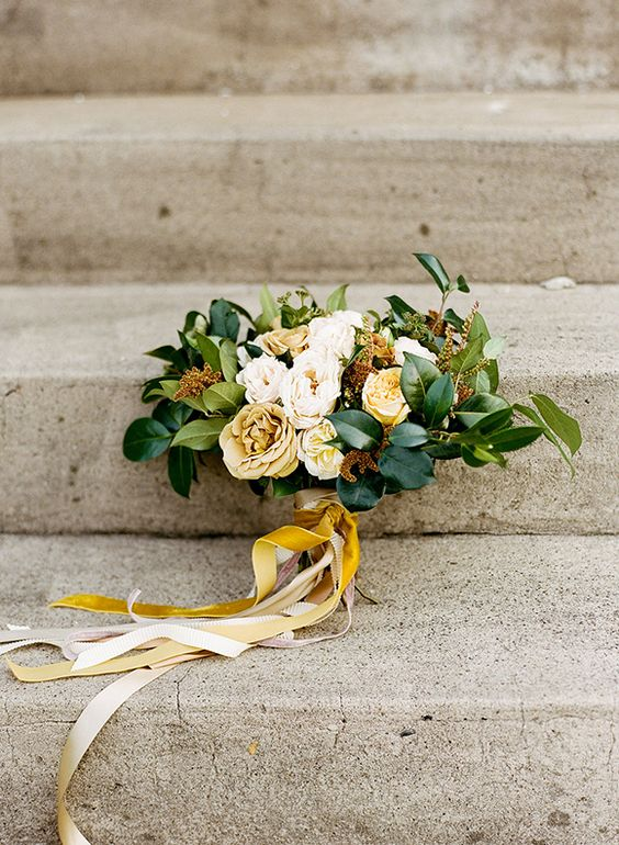 a creamy and yellow bridal bouquet with leaves and mustard and yellow ribbons