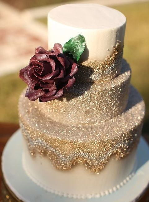 Picture Of a gold glitter wedding cake with a cream burgundy rose