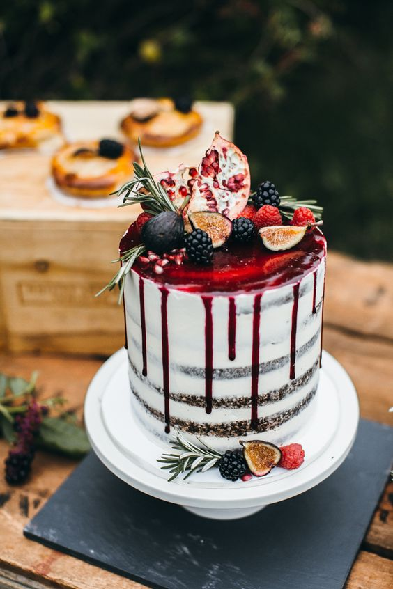 semi naked wedding cake with pomegranate drip, figs, blackberries, pomegranates