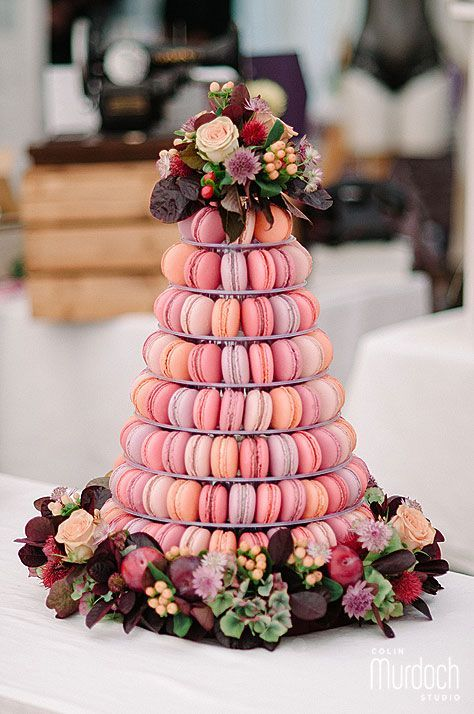 a macaron wedding tower in pink and peachy shades topped with florals and foliage