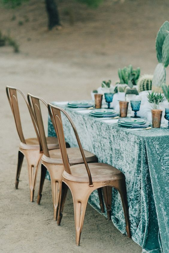 turquoise tablecloth with blue plates and glasses for a desert table setting