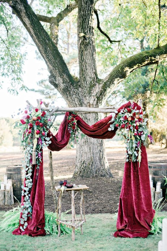 a fall wedding arch with burgundy velvet fabric, lush greenery and red roses
