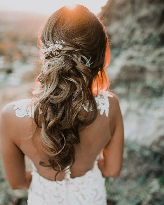twisted curly half updo accessorized with a rhinestone hairpiece on one side