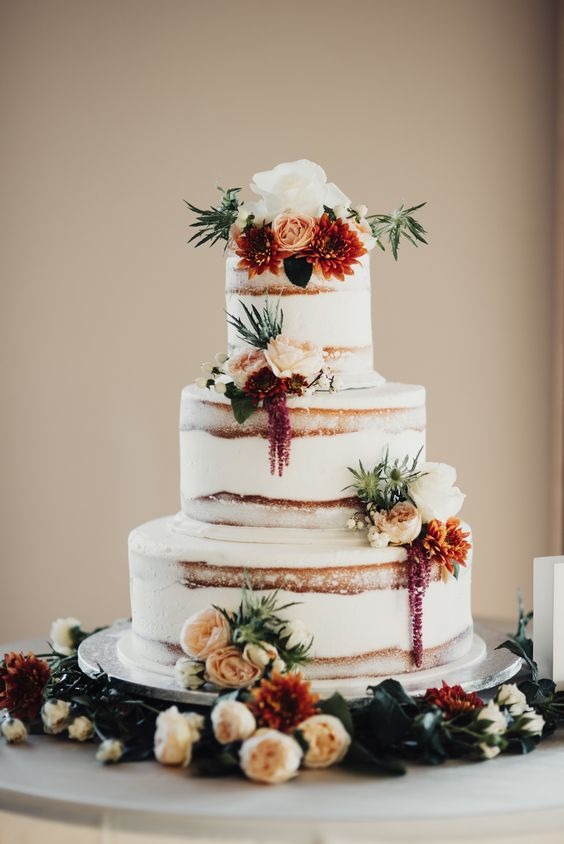 semi naked wedding cake with burgundy and orange flowers