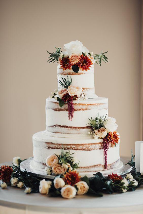 semi naked wedding cake with burgundy and orange flowers