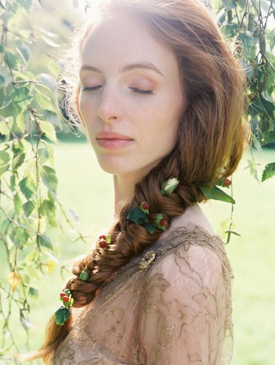 long twisted braid with greenery and berries tucked in for a boho or woodland bride