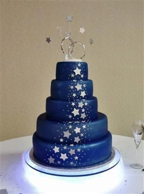 navy and silver star wedding cake with a ring and star topper