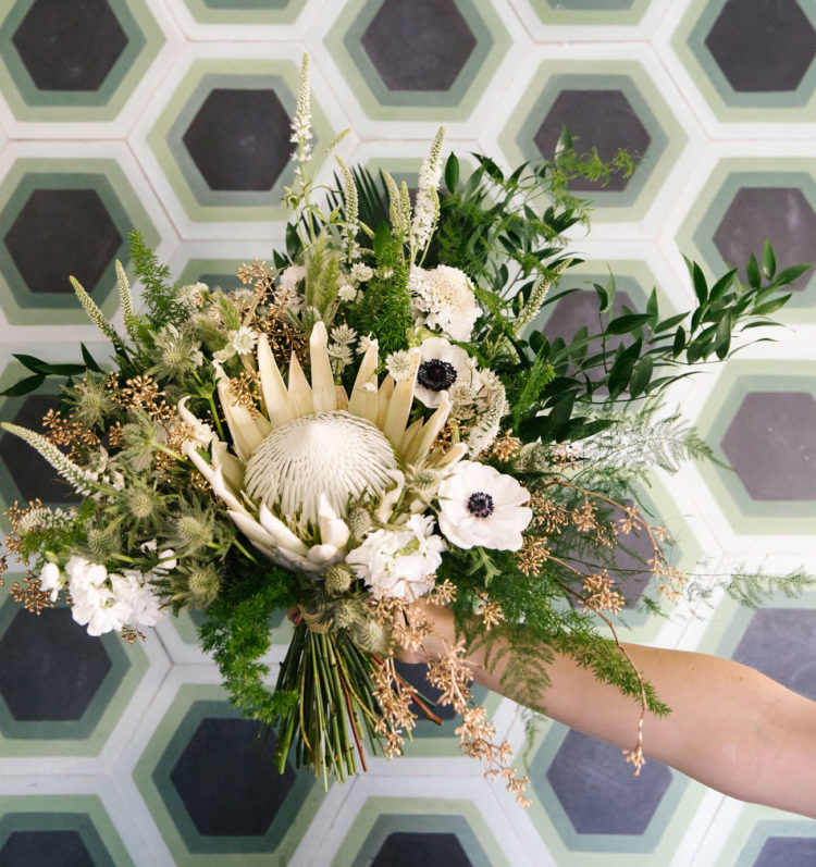 This textured lush bridal bouquet was made statement with a large king protea