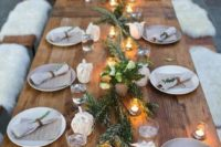 02 a cozy rustic tablescape with a greenery runner, candles and napkins accessorized with greenery and leather