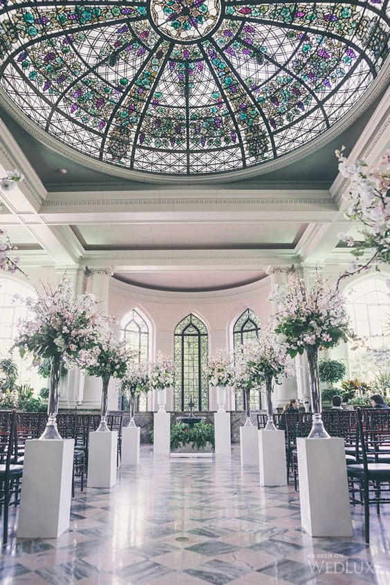 a stunning wedding ceremony space with a colorful mosaic glass dome, pink floral arrangements to line up the aisle