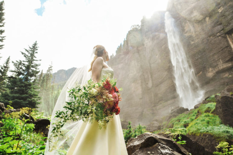The bride had a textural cascading bouquet with red, pink and white blooms and lots of greenery
