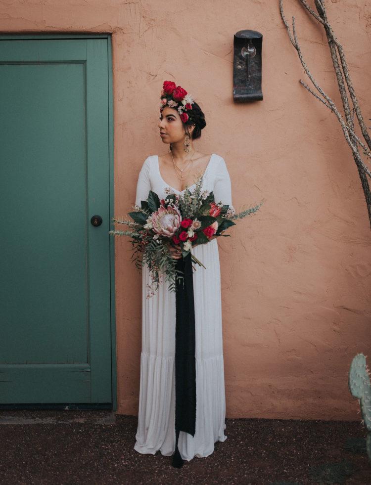 Die Braut trug ein einfaches weißes Kleid mit langen ärmeln und einem tiefen Schnitt
