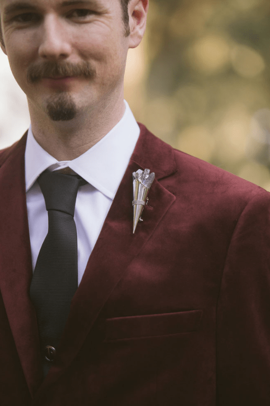 The groom preferred a burgundy velvet jacket, a black tie and pants and a crystal boutonniere matching the bride's crown