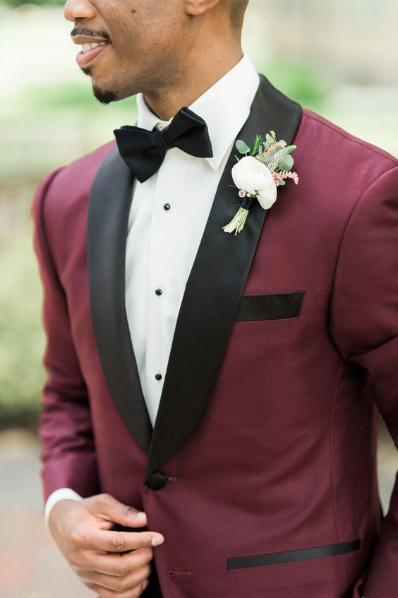 a burgundy and black wedidng suit with a white shirt and a black bow tie