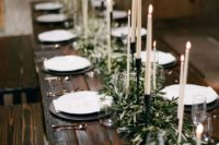 03 a dark stained wooden table with an olive branch table runner and candles