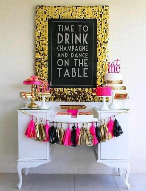 a drink bar decorated with a large gold sequin sign and a colorful tassel garland