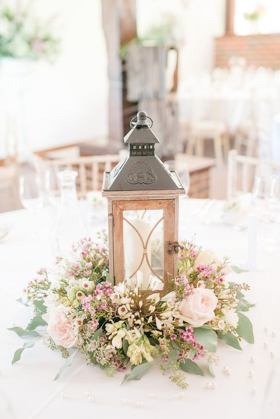 a metal candle lantern on a lush wildflower-style floral arrangement