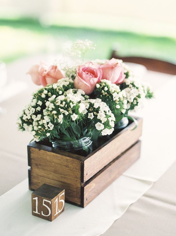 a pallet box with jars with white and pink blooms is a simple idea for a rustic wedding