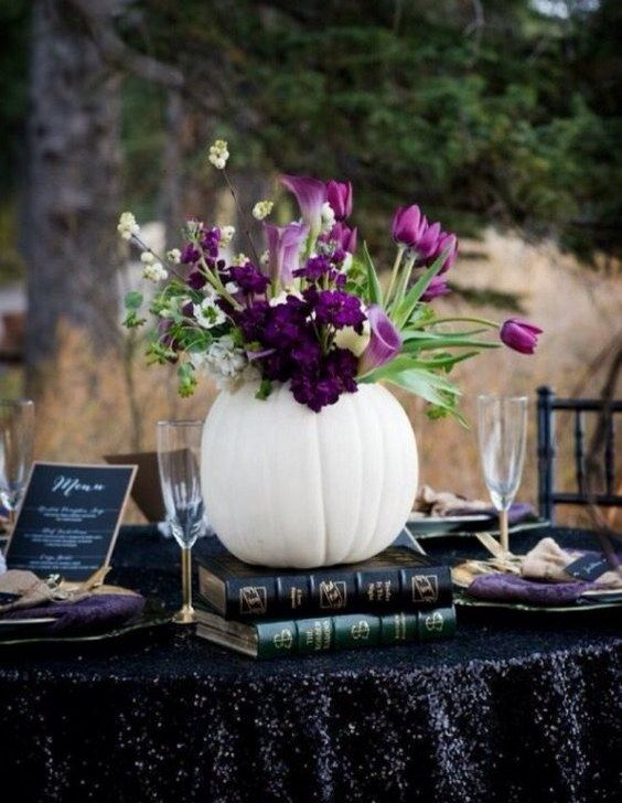 a white pumpkin used as a vase for purple flowers and greenery stands out