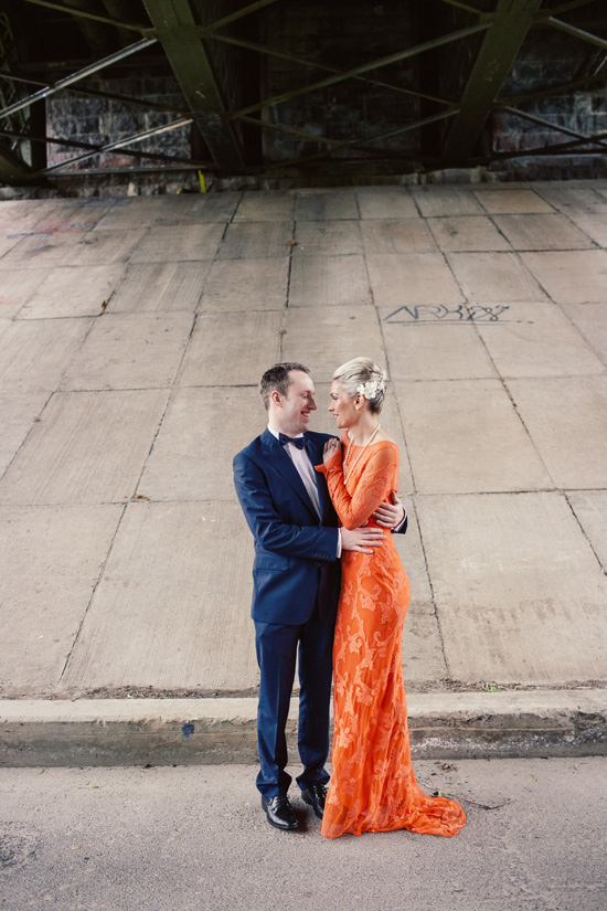 the bride rocking a bold orange lace wedding dress with long sleeves and a strand of pearls