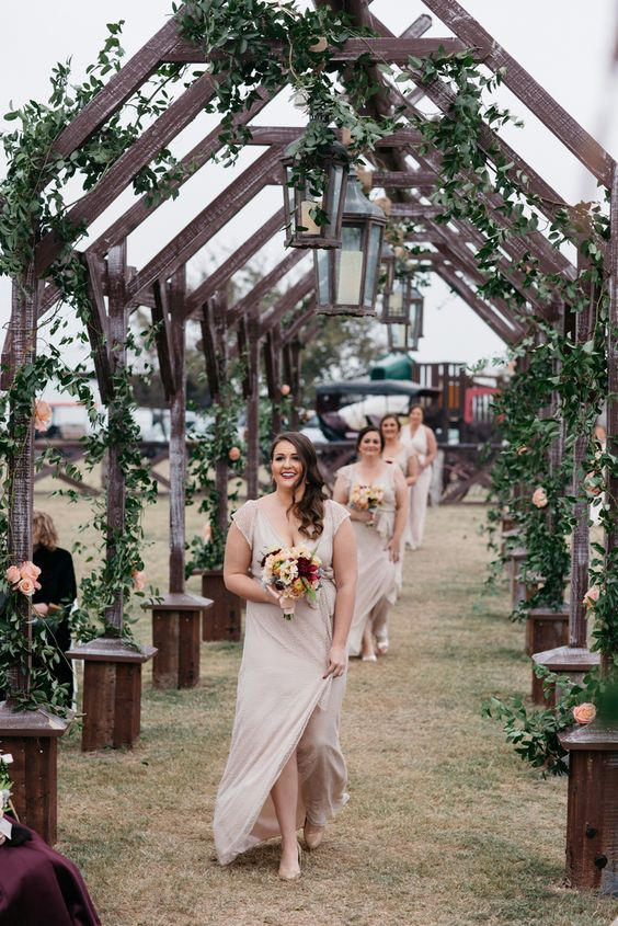 unique wedding aisle with wood arches interwoven with greenery and decorated with candle lanterns