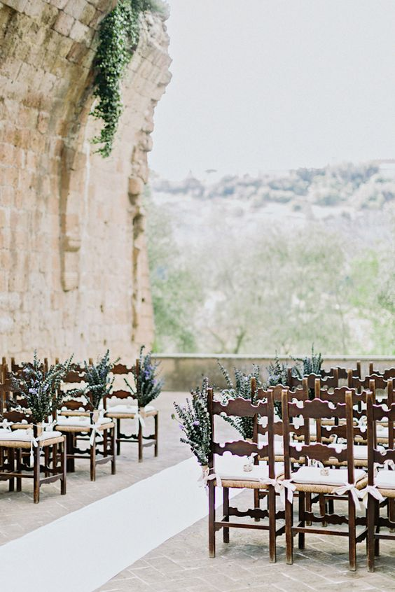 a castle terrace used as a ceremony space, chairs decorated with blooms, and a grorgeous backdrop