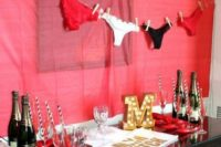 04 a fun drink station with a red wall, gold balloons and a panties garland