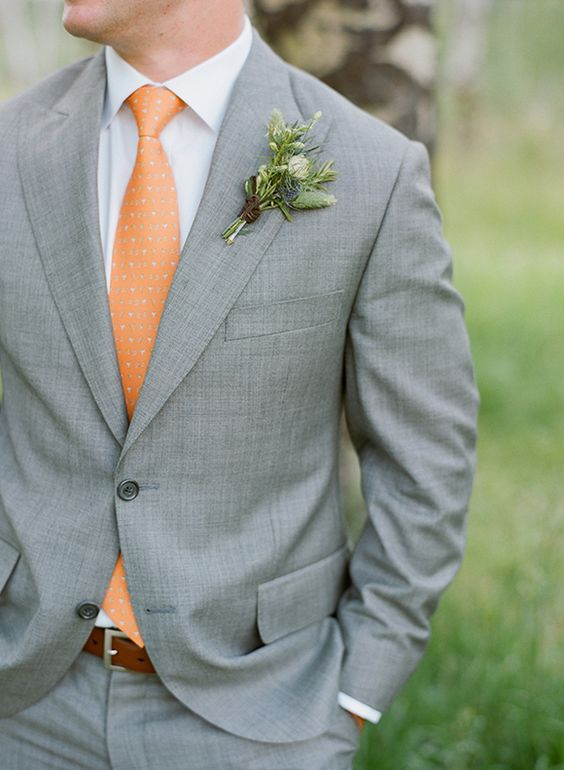 a grey suit, a white shirt and a printed orange tie for a chic look with a colorful touch