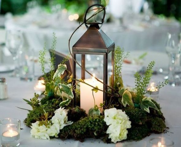 a metal candle lantern on a moss piece, with herbs and white blooms looks amazing for a woodland wedidng tablescape