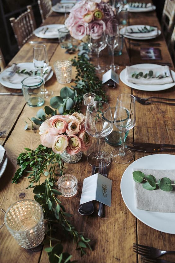 greenery runners, pink flower centerpieces and candles with no tablecloth