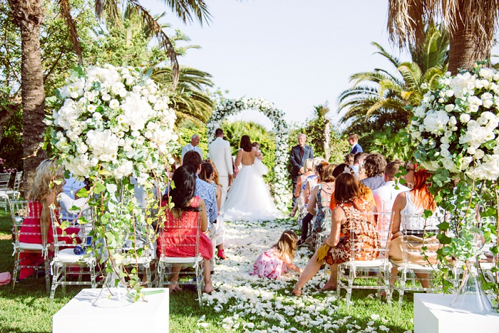A lush white floral arch and topiaries defined the wedding ceremony space