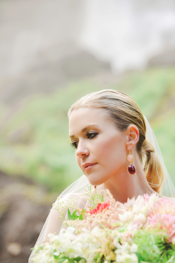 The bride was wearing statement earrings with blush and burgundy stones
