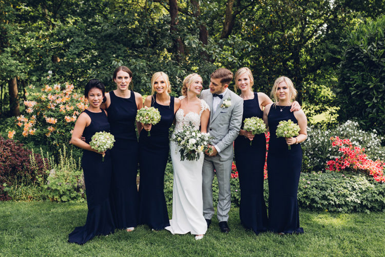 The bridesmaids were wearing navy halter neckline dresses and were carrying green bouquets