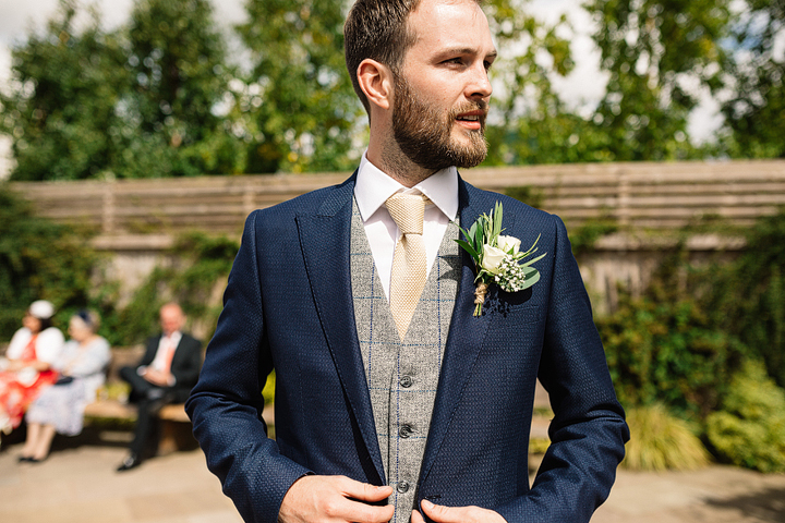 The groom was wearing a navy suit with a grey waistcoat and a beige tie