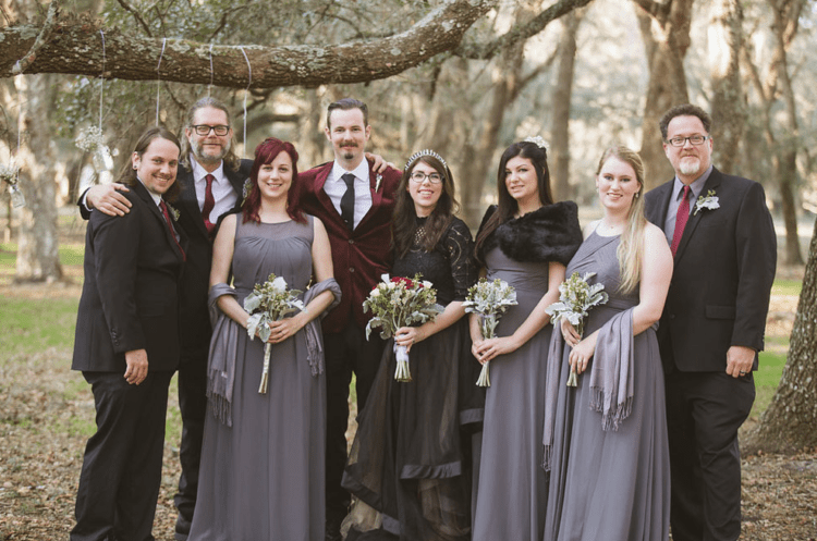 The groomsmen were wearing black suits, grey or white shirts and red ties