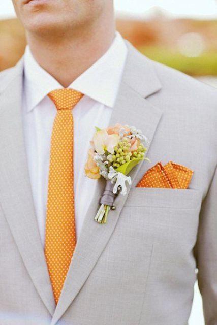 einen leichten grauen Anzug mit einem weißen Hemd und eine polka dot orange Krawatte und ein Taschentuch