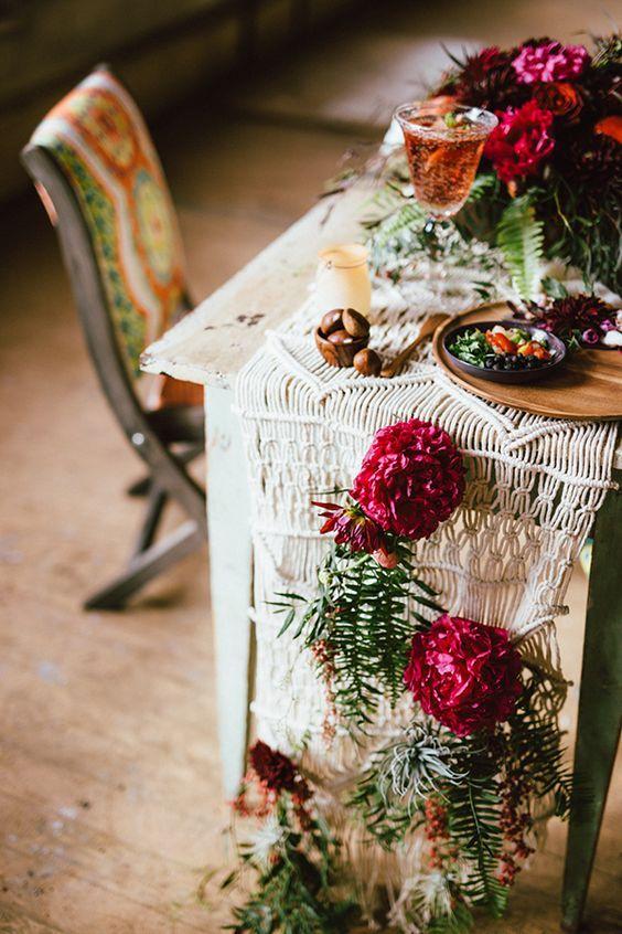 eine Makramee-Tischläufer mit karminroten Blüten und grün für ein boho Herbst Hochzeit