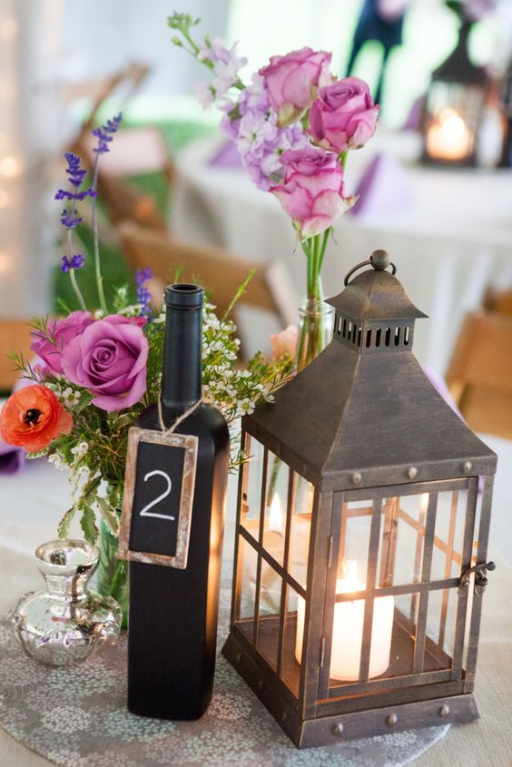 a metal candle lantern, a fuchsia floral arrangement and a chalkboard bottle table number for a vineyard celebration