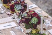 05 a wooden table with moss and bold burgundy and green centerpieces, candles and simple cutlery