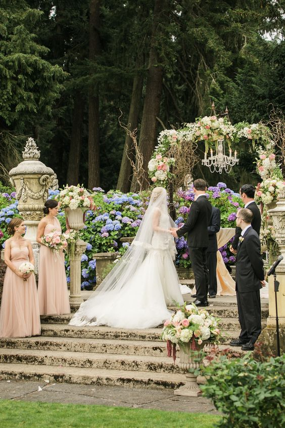 refined castle garden turned into a ceremony space, gorgeous blooms and urns with florals