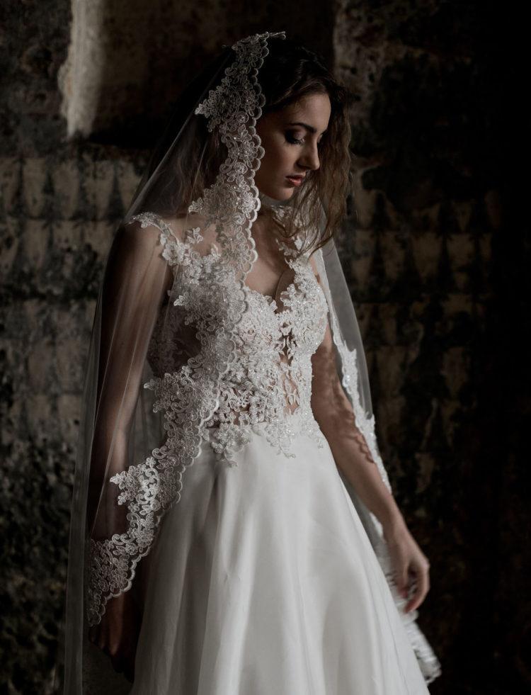 War die Braut trägt einen wunderschönen Spitzen-Mieder V-Hals-Hochzeit Kleid mit einem seidenen Rock und eine mantilla Schleier mit Spitze