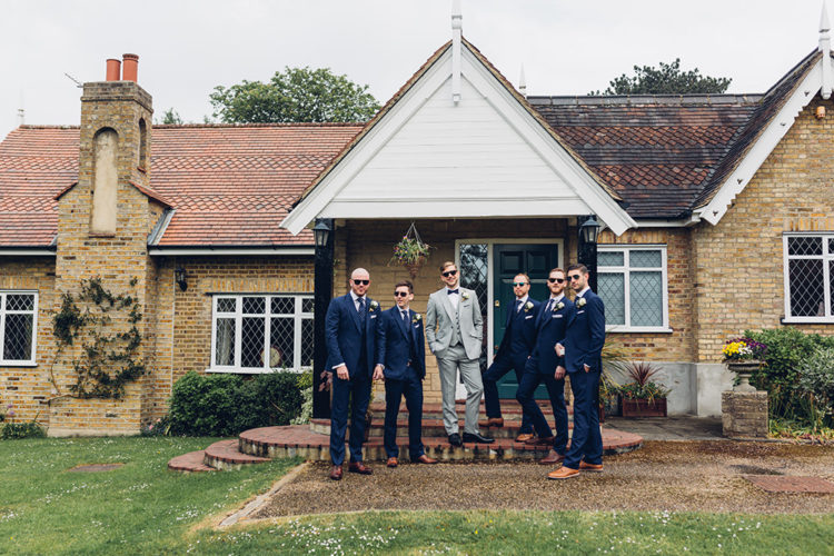 The groomsmen rocked navy suits with polka dot ties and cognac shoes