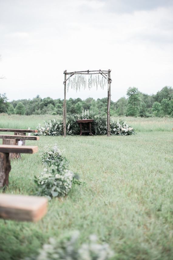 The wedding arch was rustic and boho, made of wood and with hanging wildflowers