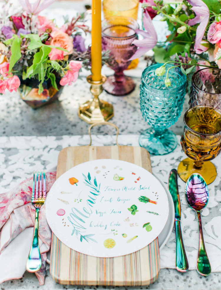 The wedding table setting was done with colorful glasses, bold blooms, printed menus and colorful cutlery