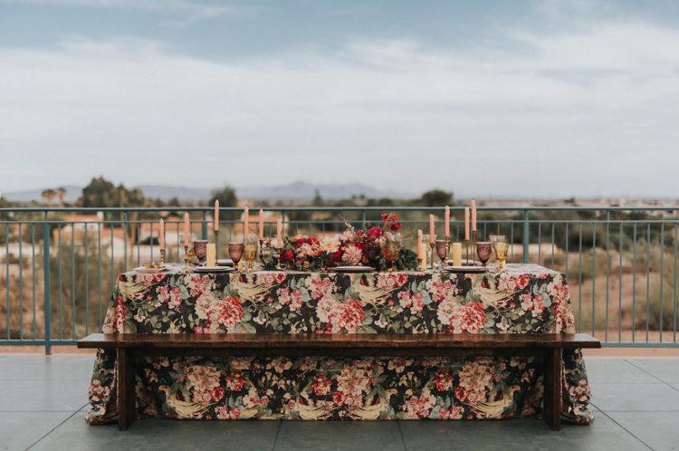 Hochzeit Tisch gelegt wurde, mit einem Fett floral Tischdecke, blush Kerzen und Teller und einen wunderschönen floralen Herzstück