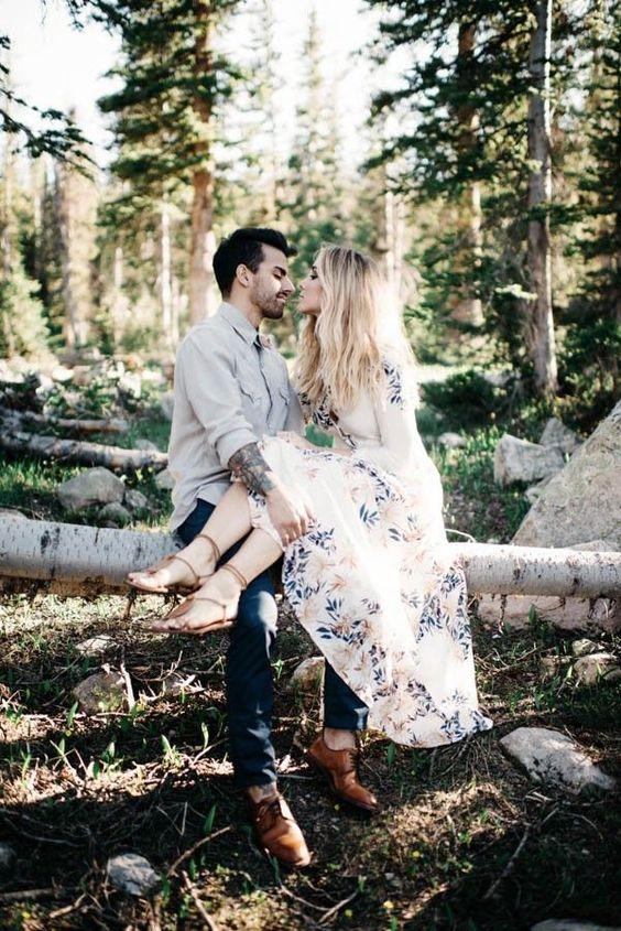 eine boho paar mit einem Braut-zu-sein in einem geblümten Kleid, Ledersandalen und einem tätowierten Bräutigam in jeans