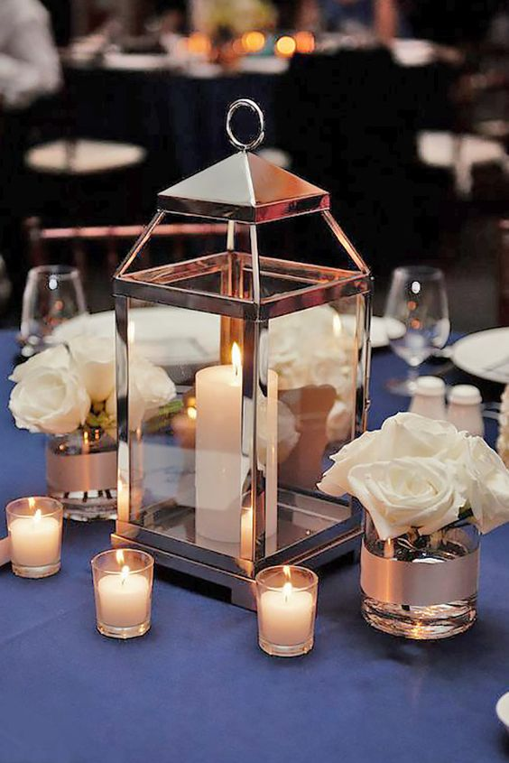 a modern shiny metal candle lantern, some small candles and white rose arrangements for an elegant wedding