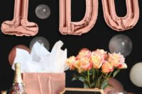 06 a pink champagne bar with large balloons and glitter bottles