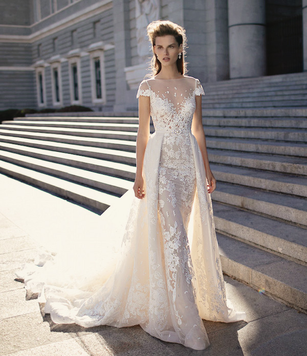 a sheath lace wedding dress with an illusion neckline and a lace overskirt