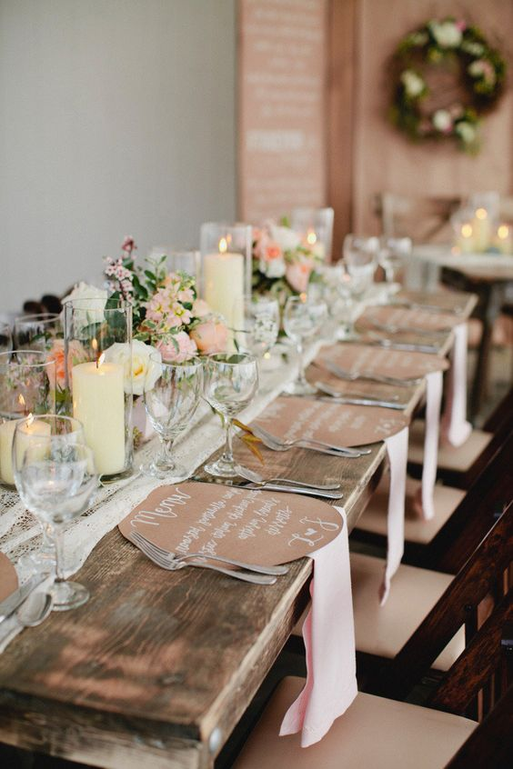 a wooden table with a lace table runner, candles and pink blooms, kraftpaper menus